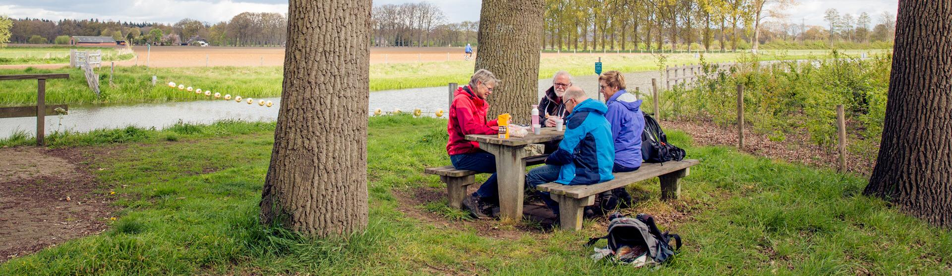mensen die drinken koffie aan de picknicktafel langs de rivier de Berkel.