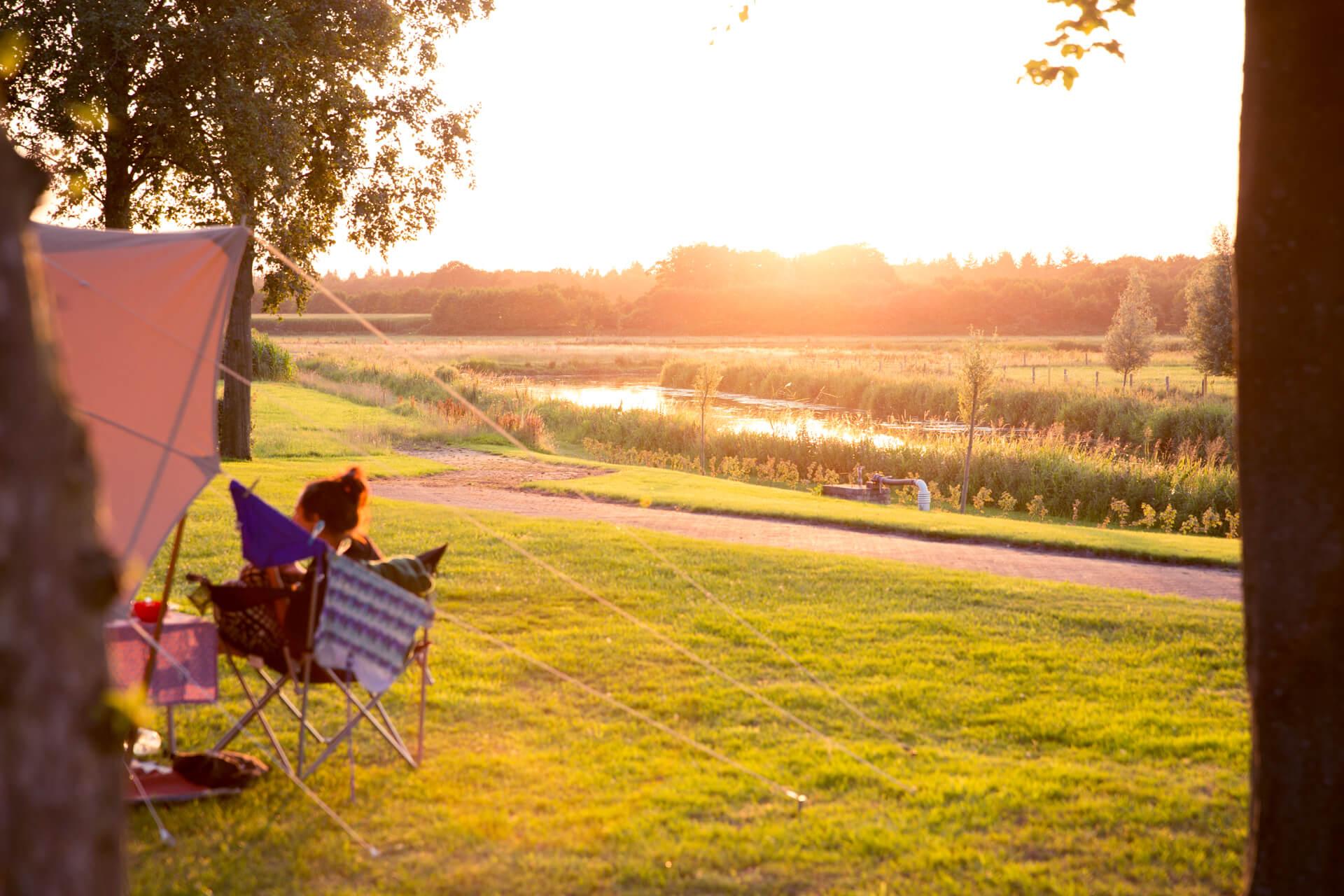 Ondergaande zon vanuit de tent op camping domein groot Besselink. gelegen aan de rivier de Berkel.