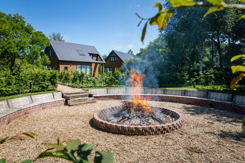 grote vuur plaats met op de achtergrond vakantie villa's in de groene natuur