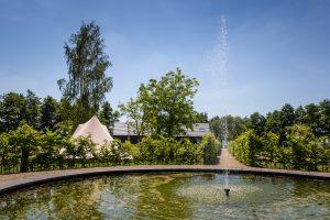 Je ziet de fontein met daarom heen tenten caravans en de vakantie villa's