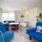 Studio met slaapbank, tafel, bed, keuken, planten, badkamer