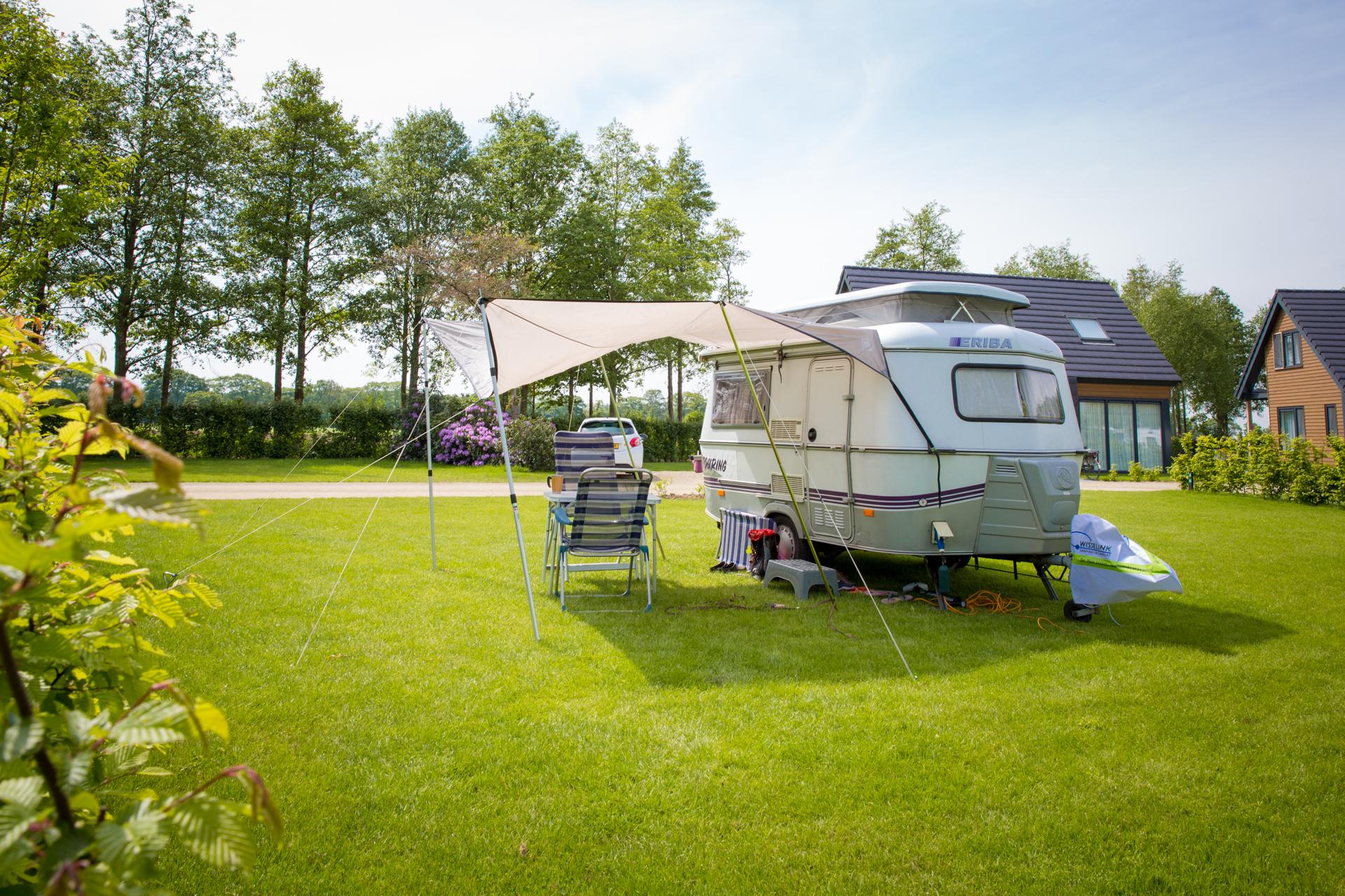een caravan met luivel op het gras met bomen en vakantie villa's op de achtergrond.